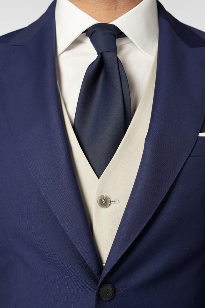 Détails sur le costume bleu, la chemise blanche, le gilet gris clair et la cravate bleue