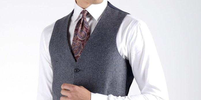 Gilet à fines rayures gris porté sur une chemise blanche et une cravate à motifs bordeaux