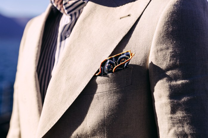 Detail on beige jacket with puff fold folded blue pocket square