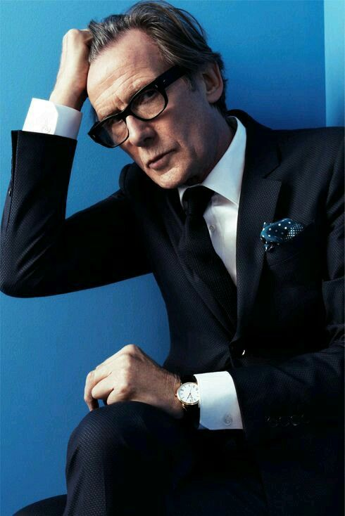 Actor Bill Nighy posing while wearing a dark suit, white shirt, black tie and a blue polka dot pocket square puff folded