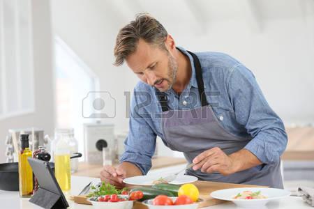 46409626-el-hombre-en-el-plato-de-la-cocina-de-la-cocina-y-el-uso-de-la-tableta-digital