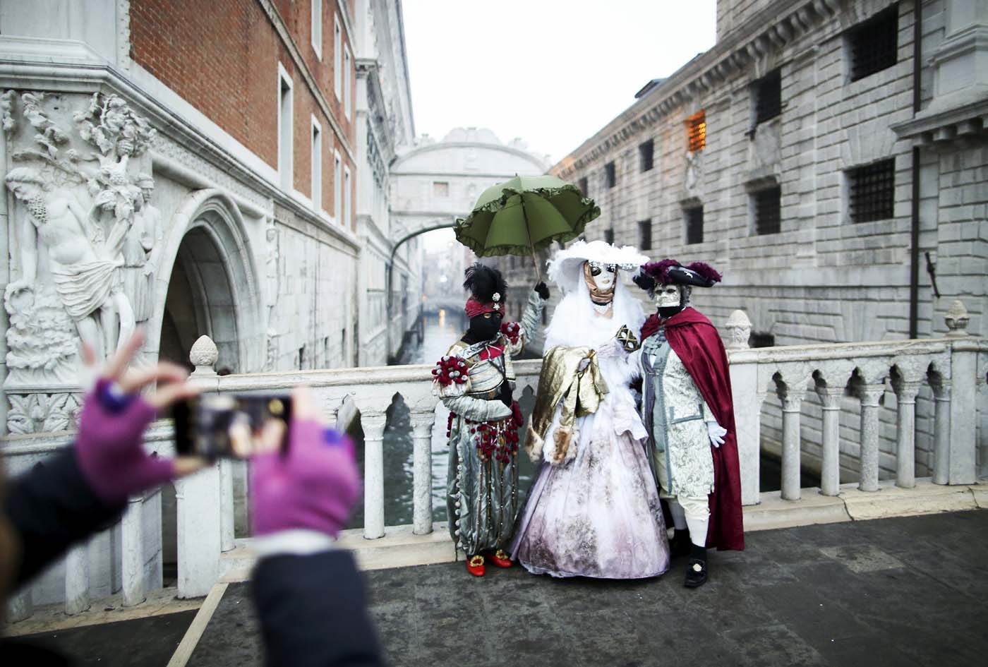 A tourist takes a picture of masked revellers (R) standing in front of the Ponte dei Sospiri (Bridge of Sighs) during the Venice Carnival January 30, 2016. REUTERS/Alessandro Bianchi