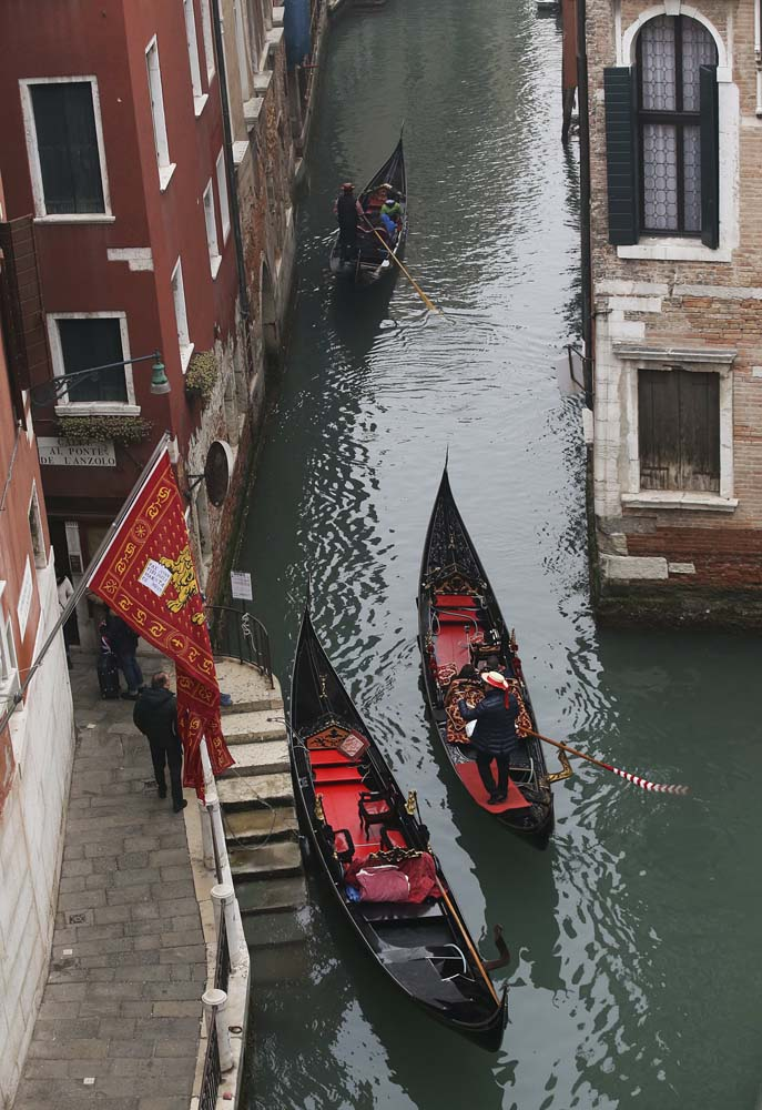Gondoliers row along a canal near St. Mark's Square in Venice January 30, 2016. REUTERS/Alessandro Bianchi