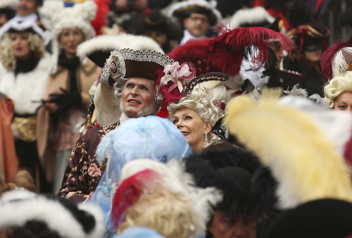 Revellers watch as the traditional Columbine descends from Saint Mark's tower bell on an iron cable during the Venice Carnival, January 31, 2016. REUTERS/Alessandro Bianchi