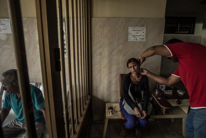 Un médico pincha la oreja de Soraya Rodríguez durante una prueba de sangre para detectar la malaria en una clínica de Tumeremo. Credit Meridith Kohut para The New York Times