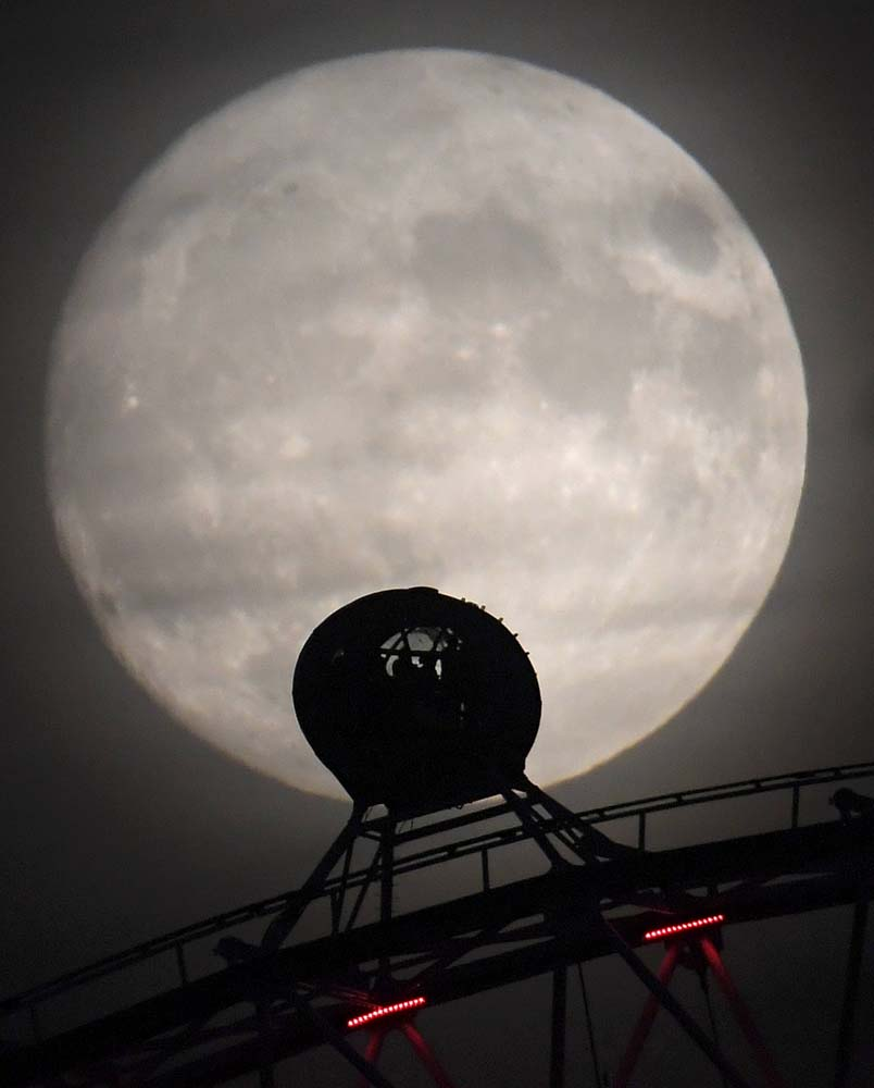 """The moon is seen behind the London Eye wheel a day before the """"supermoon"""" spectacle in London, Britain, November 13, 2016. REUTERS/Toby Melville"""