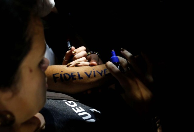 "A woman writes ""Fidel lives"" on her forearm during a massive tribute to Cuba's late President Fidel Castro on Revolution Square in Havana, Cuba, November 29, 2016. REUTERS/Stringer EDITORIAL USE ONLY. NO RESALES. NO ARCHIVE"