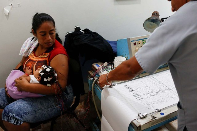 """Iberis Vargas (L), holds her 7-month-old daughter, Geovelis Ramos, a neurological patient being treated with anticonvulsants, during an electroencephalogram in a clinic in La Guaira, Venezuela February 4, 2017. REUTERS/Carlos Garcia Rawlins SEARCH """"EPILEPSY CARACAS"""" FOR THIS STORY. SEARCH """"WIDER IMAGE"""" FOR ALL STORIES."""