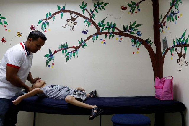"""Miguel Anton (L) comforts his son Jose Gregorio Anton, 11, a neurological patient being treated with anticonvulsants, after a blood test at a clinic in La Guaira, Venezuela February 20, 2017. REUTERS/Carlos Garcia Rawlins SEARCH """"EPILEPSY CARACAS"""" FOR THIS STORY. SEARCH """"WIDER IMAGE"""" FOR ALL STORIES."""