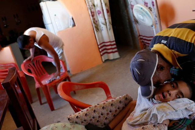 """Jose Gregorio Anton (R), 11, a neurological patient being treated with anticonvulsants, is kissed by a neighbour at his house in La Guaira, Venezuela February 15, 2017. REUTERS/Carlos Garcia Rawlins SEARCH """"EPILEPSY CARACAS"""" FOR THIS STORY. SEARCH """"WIDER IMAGE"""" FOR ALL STORIES."""