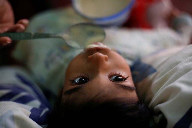 """Norymar Torres, feeds his son Leonardo Colmenares, 6, a neurological patient being treated with anticonvulsants, at their house in Caracas, Venezuela January 16, 2017. REUTERS/Carlos Garcia Rawlins SEARCH """"EPILEPSY CARACAS"""" FOR THIS STORY. SEARCH """"WIDER IMAGE"""" FOR ALL STORIES."""