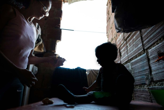 The mother of Venezuelan Rebeca Leon, who scavanges for food in the streets of Caracas, feeds her grandson at their house in Petare shantytown, on February 22, 2017. Venezuelan President Nicolas Maduro is resisting opposition efforts to hold a vote on removing him from office. The opposition blames him for an economic crisis that has caused food shortages. / AFP PHOTO / FEDERICO PARRA / TO GO WITH AFP STORY by Alexander Martinez
