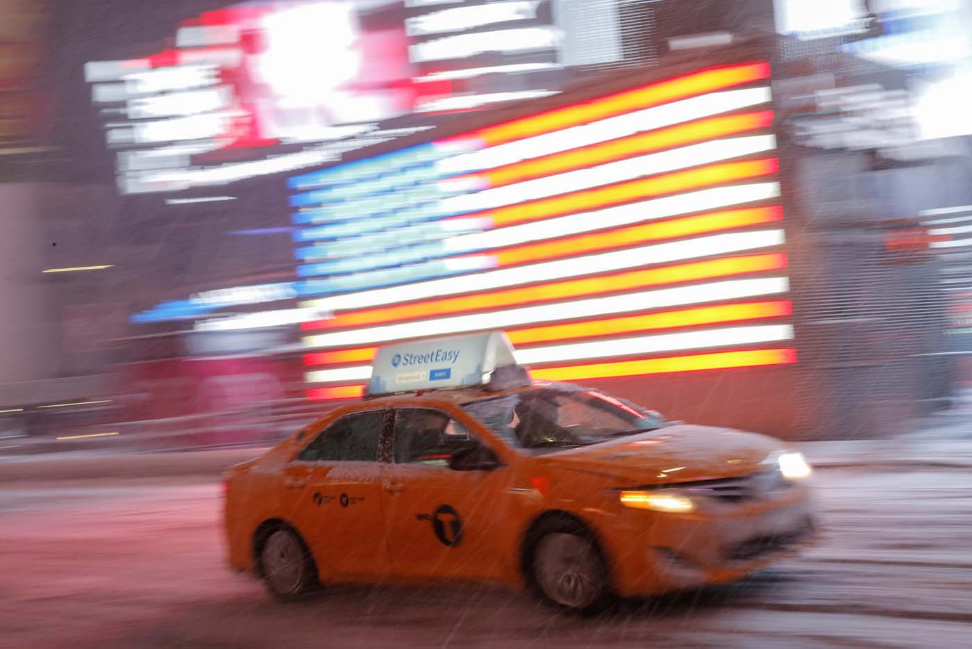 A taxi cab drives through Times Square as snow falls in Manhattan, New York, U.S., March 14, 2017. REUTERS/Andrew Kelly