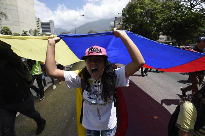 Venezuelan opposition activists shout slogans during a protest against the government of President Nicolas Maduro on April 6, 2017 in Caracas. The center-right opposition vowed fresh street protests -after earlier unrest left dozens of people injured - to increase pressure on Maduro, whom they blame for the country's economic crisis. / AFP PHOTO / JUAN BARRETO