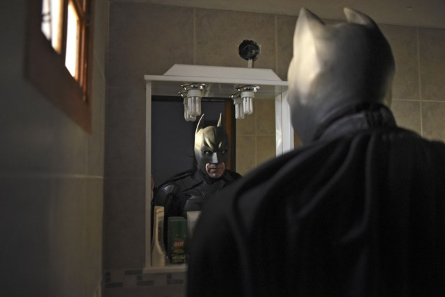 Argentine Batman, looks at his reflexion in a mirror after leaving his house in La Plata, 60 kilometres south of Buenos Aires, on June 2, 2017.  The Argentine Batman has made La Plata children's hospital a target of laughter and treats against pain. / AFP PHOTO / Eitan ABRAMOVICH
