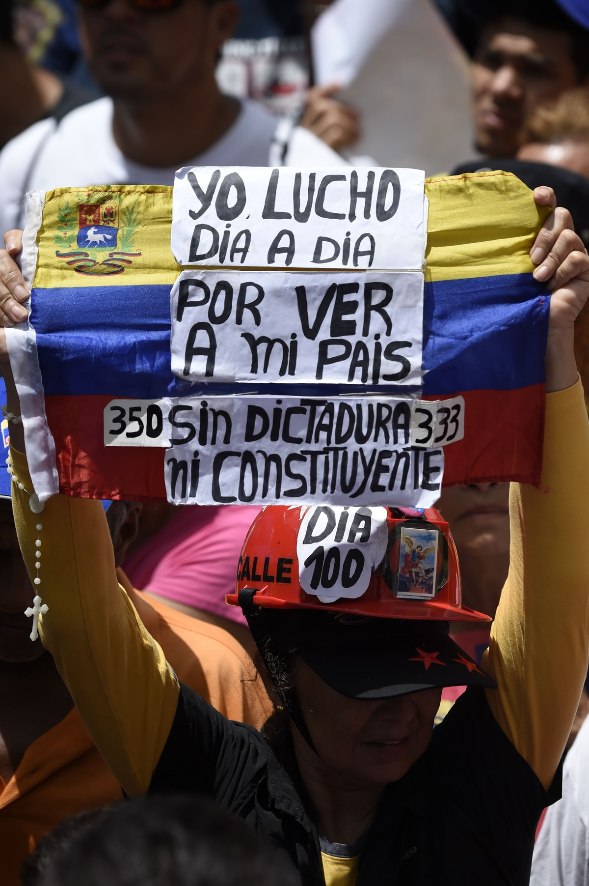 An opposition activist demonstrates against Venezuelan President Nicolas Maduro in Caracas, on July 9, 2017. Venezuela hit its 100th day of anti-government protests on Sunday, one day after its most prominent political prisoner, Leopoldo Lopez, vowed to continue his fight for freedom after being released from jail and placed under house arrest. At least 91 people have died since non-stop street protests began on April 1. / AFP PHOTO / Juan BARRETO