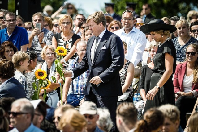 """Dutch King Willem-Alexander (C) and Queen Maxima (R) attend the unvealing of the National Monument for the MH17 victims in Vijfhuizen, on July 17, 2017. Three years after Flight MH17 was shot down by a missile over war-torn Ukraine, more than 2,000 relatives gather to unveil a """"living memorial"""" to their loved ones. A total of 298 trees have been planted in the shape of a green ribbon, one for each of the victims who died on board the Malaysia Airlines flight en route from Amsterdam to Kuala Lumpur. / AFP PHOTO / ANP / Remko de Waal / Netherlands OUT"""