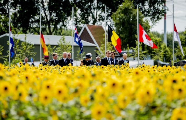 "Dutch King Willem-Alexander (3rdR) and Queen Maxima (C) attend the unveiling of the National Monument for the MH17 victims in Vijfhuizen on July 17, 2017. Three years after Flight MH17 was shot down by a missile over war-torn Ukraine, more than 2,000 relatives gather to unveil a ""living memorial"" to their loved ones. A total of 298 trees have been planted in the shape of a green ribbon, one for each of the victims who died on board the Malaysia Airlines flight en route from Amsterdam to Kuala Lumpur. The flowers also represent ""the sunflower fields in eastern Ukraine where some parts of the plane wreckage were found"". / AFP PHOTO / ANP / Remko de Waal / Netherlands OUT"