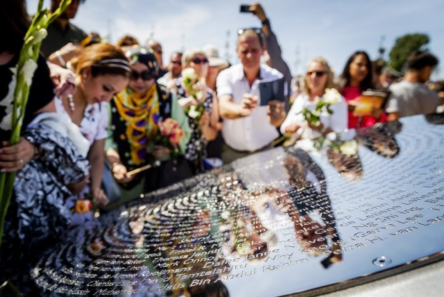 "Relatives attend the unveiling of the National Monument for the MH17 victims in Vijfhuizen, on July 17, 2017.  Three years after Flight MH17 was shot down by a missile over war-torn Ukraine, more than 2,000 relatives gather to unveil a ""living memorial"" to their loved ones. A total of 298 trees have been planted in the shape of a green ribbon, one for each of the victims who died on board the Malaysia Airlines flight en route from Amsterdam to Kuala Lumpur. The flowers also represent ""the sunflower fields in eastern Ukraine where some parts of the plane wreckage were found"". / AFP PHOTO / ANP / Remko de Waal / Netherlands OUT"