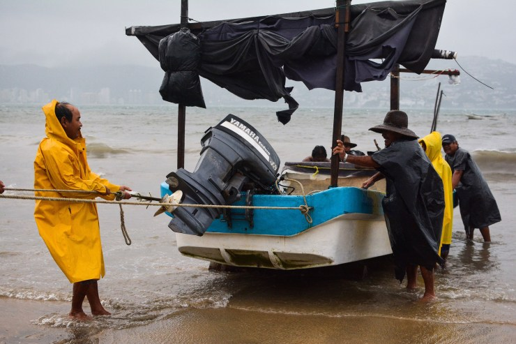 Fishermen take their boats out of the sea in anticipation of the arrival of hurricane Max in Acapulco, Guerrero state, Mexico on September 14, 2017.  Hurricane Max formed off the southwestern coast of Mexico on Thursday, triggering warnings of life-threatening storm conditions for a long stretch of coastal communities including the resort city of Acapulco, forecasters said. / AFP PHOTO / FRANCISCO ROBLES