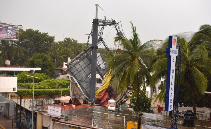 A billboard knocked down by strong winds is seen before the arrival of hurricane Max in Puerto Marquez, Guerrero state, Mexico on September 14, 2017.  Hurricane Max formed off the southwestern coast of Mexico on Thursday, triggering warnings of life-threatening storm conditions for a long stretch of coastal communities including the resort city of Acapulco, forecasters said. / AFP PHOTO / FRANCISCO ROBLES