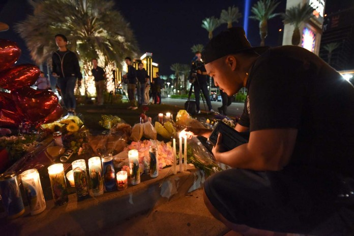 Edrian Pateno of Corona, California lights candles at a makeshift memorial near the Mandalay Hotel on the Las Vegas Strip, in Las Vegas, Nevada on October 3, 2017, after a gunman killed 58 people and wounded more than 500 others, before taking his own life, when he opened fire from a hotel on a country music festival. Police said the gunman, a 64-year-old local resident named as Stephen Paddock, had been killed after a SWAT team responded to reports of multiple gunfire from the 32nd floor of the Mandalay Bay, a hotel-casino next to the concert venue. / AFP PHOTO / Robyn Beck