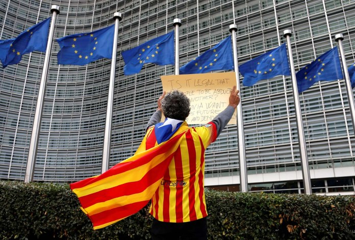 Catalan Raimon Castellvi wears a flag with an Estelada (Catalan separatist flag) as he protests outside the European Commission in Brussels after Sunday's independence referendum in Catalonia, Belgium, October 2, 2017. REUTERS/Francois Lenoir