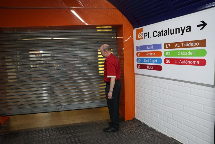 A worker closes an entrance gate to Catalunya Square subway station during a partial regional strike called by pro-independence parties and unions in Barcelona, Spain, October 3, 2017. REUTERS/Susana Vera