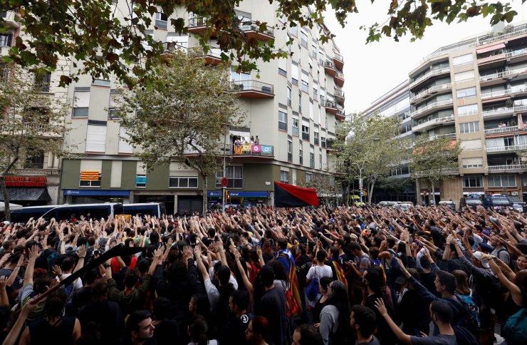 People raise hands and shout slogans outside People's Party (PP) regional headquarters in Barcelona, Spain, October 3, 2017. REUTERS/Juan Medina