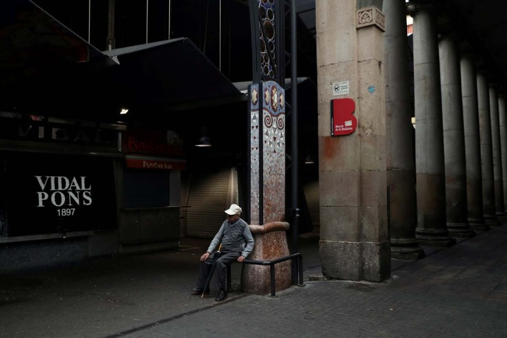 An old man sits outside an almost closed La Boqueria market during a partial regional strike called by pro-independence parties and unions in Barcelona, Spain, October 3, 2017. REUTERS/Susana Vera TPX IMAGES OF THE DAY