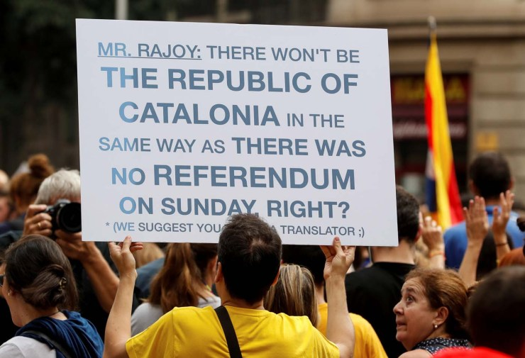 A man holds up a banner during a demonstration called to protest against police actions during the banned independence referendum in Barcelona, Spain October 3, 2017. REUTERS/Yves Herman