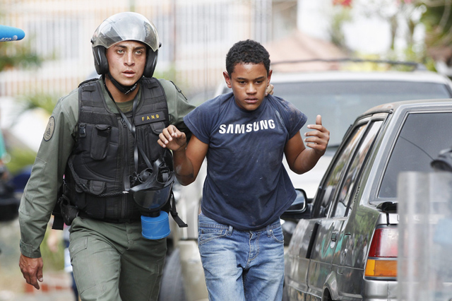 An anti-government protester is detained by national guard after clash with guard at the end of a march in Caracas