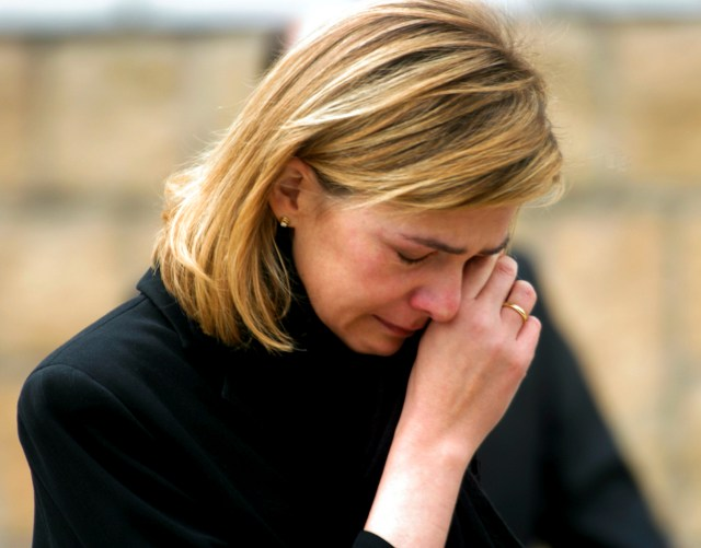 File photo of Spain's Infanta Cristina wiping her tears as she leaves Madrid's Almudena cathedral after attending the state funeral for the 190 victims of the Madrid train bombings