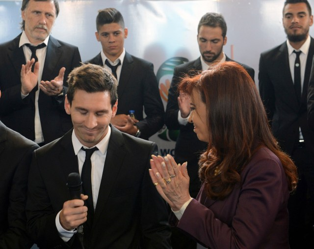 Argentine President Cristina Fernandez de Kirchner applauds next to soccer player Lionel Messi as Argentina's national soccer team arrives at the Argentine Football Association in Buenos Aires