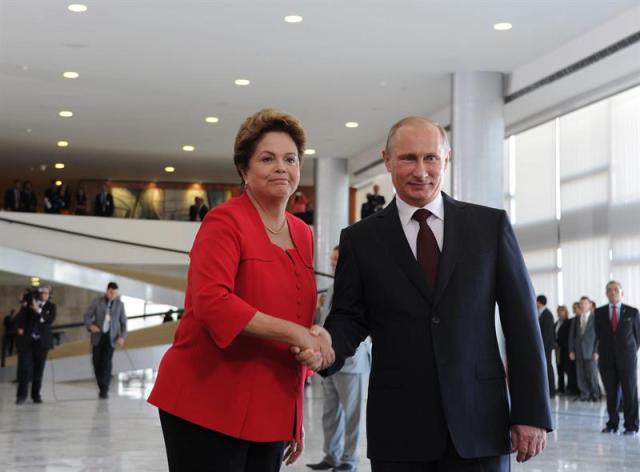 . El presidente de Rusia, Vladimir Putin (d), y su homóloga en Brasil, Dilma Rousseff (i), se saludan durante la ceremonia de bienvenida de Putin en el palacio Planalto, en Brasilia, Brasil. Foto EFE