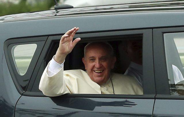 El papa Francisco saluda a los ciudadanos mientras se dirige al centro de la ciudad a bordo de un pequeño utilitario tras aterrizar en Seúl (EFE)