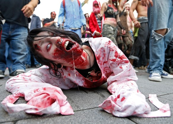 "A participant crawls on the ground during a ""Zombie Walk"" in Strasbourg"