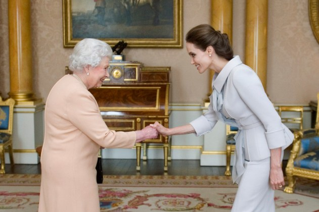 Actress Angelina Jolie is greeted by Britain's Queen Elizabeth before being presented with the Insignia of an Honorary Dame Grand Cross of the Most Distinguished Order of St Michael and St George in London