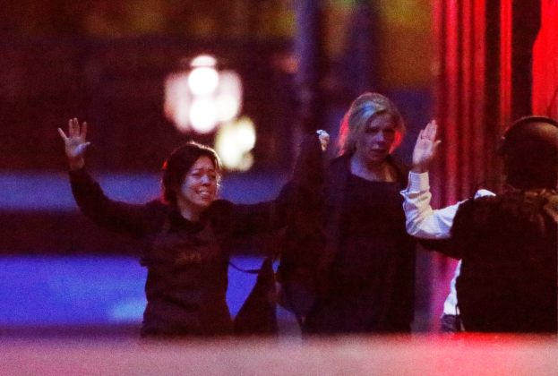 Hostages run towards a police officer (R) near Lindt Cafe, at Martin Place in central Sydney