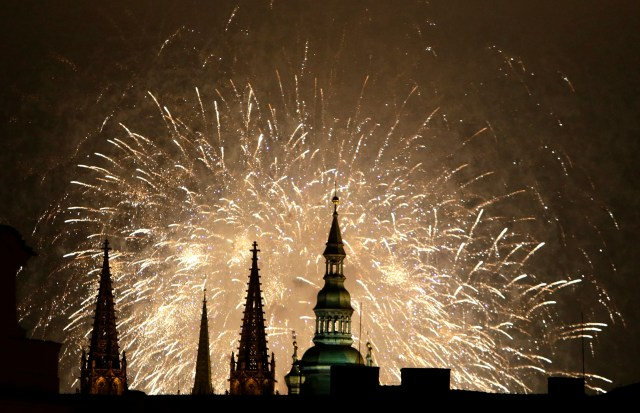 Fireworks explode over the towers of the St. Vitus Cathedral at Prague Castle to mark the first day of the new year in Prague