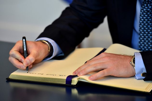 Britain's Prince Harry signs a book of condolence at the French embassy in London