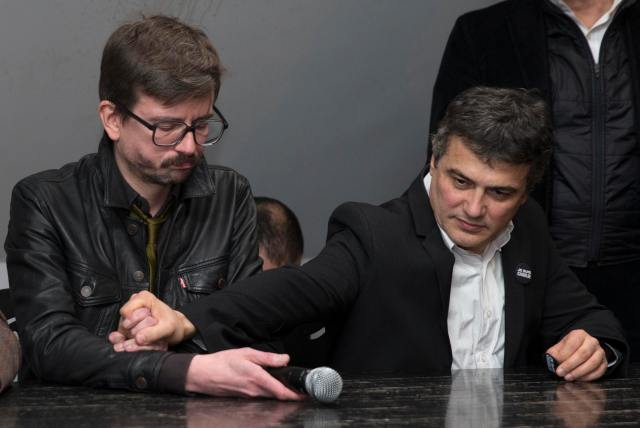Satirical French magazine Charlie Hebdo columnist Pelloux comforts cartoonist Luz as they attend a news conference at the French newspaper Liberation offices