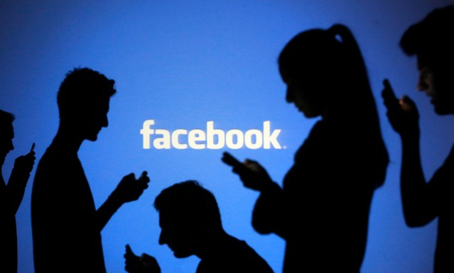 File illustration photo of people silhouetted as they pose with mobile devices in front of a screen projected with a Facebook logo