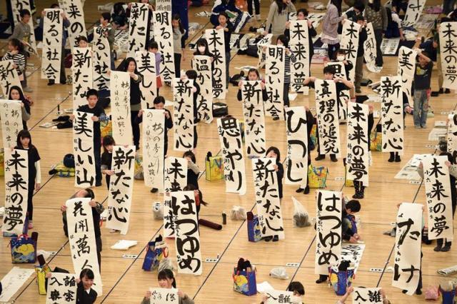 Varias chicas muestran su trabajo mientras participan en un concurso de caligrafía de Año Nuevo en Tokio (Japón) hoy, lunes 5 de enero de 2015. Más de 3.000 personas de todas las edades participaron en el certamen. EFE/Franck Robichon