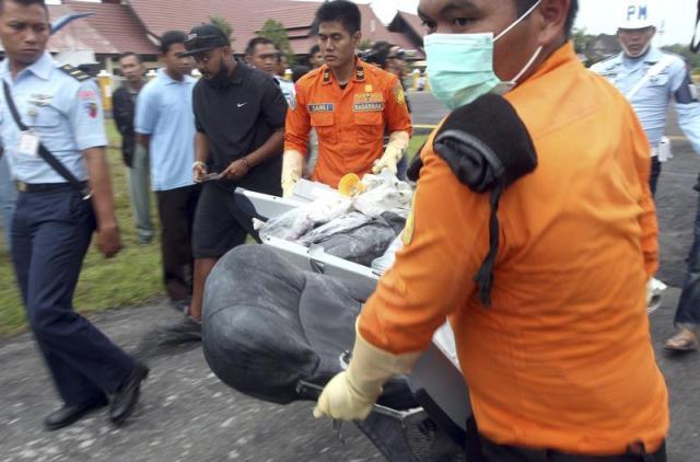 Miembros de un equipo de rescate transportan uno de los asientos del avión durante las labores de recuperación de las víctimas del siniestrado avión de AirAsia en el aeropuerto militar de Iskandar, en Pangkalan Bun (Indonesia) hoy, lunes 5 de enero de 2015. Los equipos de rescate han recuperado 34 cadáveres del avión de AirAsia accidentado hace una semana en el oeste de Indonesia, donde el mal tiempo y las fuertes corrientes dificultan las tareas de búsqueda, indicaron hoy las autoridades indonesias. EFE/Adi Weda