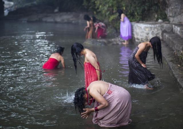 Mujeres nepalíes hindúes limpian sus pecados con un baño sagrado en el río Salinadi durante el festival Madhav Narayan en Sankhu, cerca de Katmandú (Nepal), hoy, lunes 5 de enero de 2015. Durante el mes que dura el festejo, también conocido como Swasthani Purnima, los devotos hindúes realizan ayuno y se dan un baño sagrado cada amanecer. Las solteras de casta alta rezan para encontrar un marido; las casadas lo hacen por el bienestar de sus esposos y sus familias, y los hombres piden con sus oraciones una mejor vida. EFE/Narendra Shrestha
