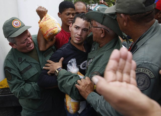 People argue with Venezuelan soldiers as they try to buy chickens at a Mega-Mercal, a subsidized state-run street market, in Caracas