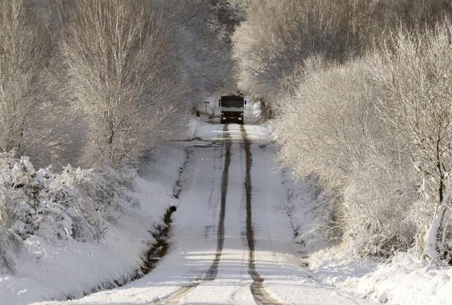 Un camión circula por una carretera nevada cerca de Monterroso, en la provincia de Lugo. La nieve, que esta mañana incluso se dejó ver en la capital lucense, está complicando la circulación por la red viaria de la provincia, especialmente en las carreteras provinciales y en las autonómicas, donde es preciso el uso de cadenas en al menos tres puertos de montaña. EFE/Eliseo Trigo