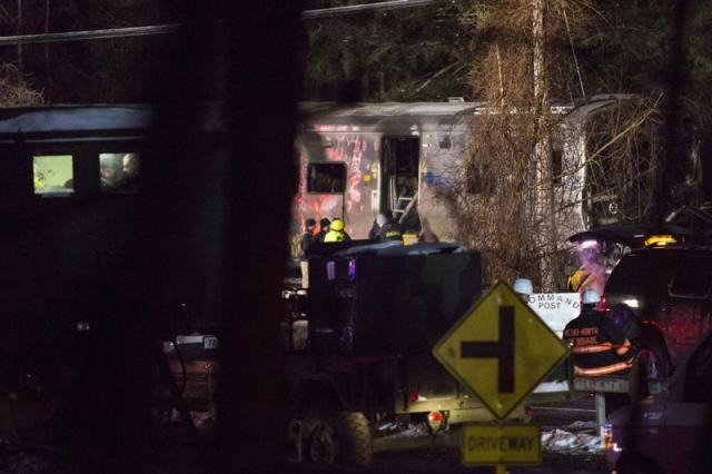 Bomberos y policía permanecen en el lugar donde se ha producido el choque entre un tren y un vehículo en Valhalla (Estados Unidos) ayer, martes 3 de febrero de 2015. Al menos siete personas murieron ayer en la localidad neoyorquina de Valhalla al arrollar un tren suburbano un vehículo que estaba detenido en las vías, informaron fuentes oficiales.  Fuentes de la Autoridad del Transporte Metropolitano (MTA, en inglés) y del condado donde se produjo el accidente dijeron que, además de las siete víctimas mortales, hay entre diez y doce heridos, algunos de ellos graves. EFE/John Taggart