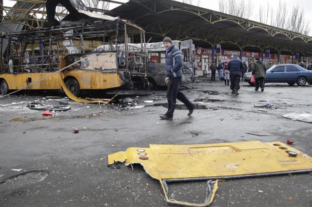 Un hombre pasa por la zona donde impactaron varios proyectiles de artillería en Donetsk (Ucrania), hoy, miércoles 11 de febrero de 2015. Al menos seis civiles murieron y otros ocho resultaron heridos por fuego de artillería en una estación de transporte público, donde impactaron en dos autobuses que quedaron completamente destruidos, y sobre la entrada de una fábrica metalúrgica. El recrudecimiento de los combates coincide con las negociaciones del Grupo de Contacto (Ucrania, Rusia y la Organización para la Seguridad y Cooperación en Europa, más los separatistas) en Minsk, donde los líderes de Ucrania, Rusia, Alemania y Francia tienen previsto reunirse para abordar un plan de paz para este ucraniano. De acuerdo con datos de la ONU, más de 5.300 personas, entre combatientes y civiles, ha muerto en los casi diez meses de conflicto armado en las regiones orientales de Ucrania. EFE/Alexander Ermochenko